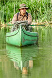 Man in old canoe on the river with backpack and hat - beautiful nature Royalty Free Stock Images