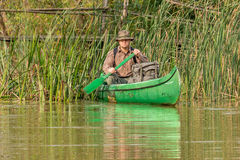 Man in old canoe on the river with backpack and hat in front of old wooden bridge Royalty Free Stock Photography