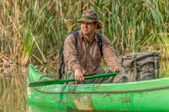 Man in old canoe on the river with backpack and hat - portrait Royalty Free Stock Photography