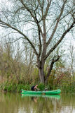Man in old canoe on the river in front of big old dead tree Royalty Free Stock Photo