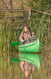 Man in old canoe on the river in front of old wooden bridge Stock Image