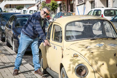 Man with an old classic yellow wolsvagen beetle Royalty Free Stock Photo