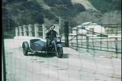 Man on old fashioned motorcycle with sidecar tossing cigarette stock video footage