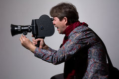 A man with an old movie camera on a gray background. Royalty Free Stock Image