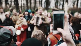 Man in old soviet soldier uniform playing accordion and sing with crowd stock footage