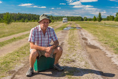 Man with old suitcase sitting on an country road in Ukraine Royalty Free Stock Image