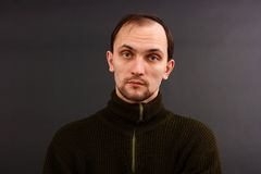 Man in an old sweater. Young man in an old sweater on a dark background. studio portrait Royalty Free Stock Photo