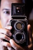 Man with old vintage camera in hands. Focus to man eyes. Vintage stylized photo of man photographer with old TLR Twin Lens Reflex royalty free stock image