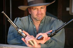 Man in old West clothing wielding two pistols. Head and torso of an unshaven cowboy looking directly at viewer with 2 pistols at the ready Royalty Free Stock Image