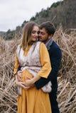Man omfamningar och kyssar gravida kvinnan bland torra vasser Royaltyfri Fotografi