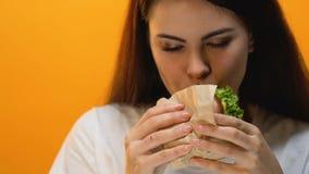 Man omhoog sluit de brengende hamburger voor vrouw, jonge dame die greedily, boulimie, eten stock video