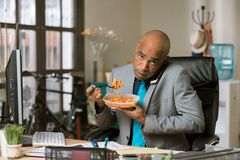 Free Man On The Phone And Eating At His Desk Stock Image - 143371751