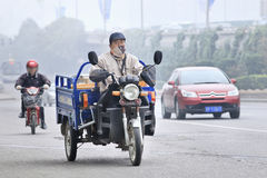 Man ona freight bike covers his mouth against smog, Beijing, China Royalty Free Stock Image