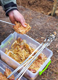 Man one hand holding the meat, other - stringing skewer Stock Images