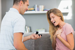 Man on one knee proposing to surprised girlfriend Stock Photography