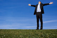 Man with open arms. Man in suit with open arms outside on grass, against a blue sky Royalty Free Stock Images