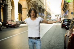 Man with Open Arms Standing in City Street. Young Man Wearing White T Shirt with Open Arms Standing in Street and Facing Camera Royalty Free Stock Photo