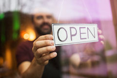 Man with open banner at bar or restaurant window. Small business, people and service concept - man with open word on banner at bar or restaurant window Royalty Free Stock Photo