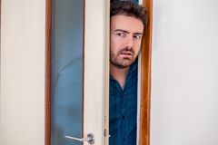 One man entering the door and spying stock photo