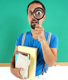 Man open-eyed with magnifier, among the books. Royalty Free Stock Photo