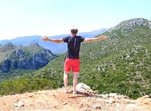 Man with open hands standing at the top of the mountain Greece royalty free stock photo