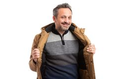 Man with open jacket and sweater. Smiling friendly man with open jacket and striped sweater as presenting winter attire in fashion concept isolated on white stock image