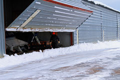 Man opening airport hangar door snow Royalty Free Stock Photos