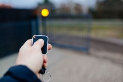 Man opening automatic property gate. With remote controller royalty free stock photo