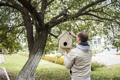Man is opening a birdhouse. To look in it Royalty Free Stock Photo