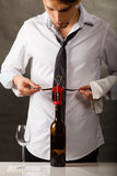Man opening bottle of wine with corkscrew Royalty Free Stock Images