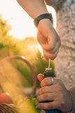 Man opening a bottle of wine at sunset and meadows Royalty Free Stock Photo