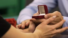 Man opening box with diamond engagement ring, woman touching his hands, proposal. Stock footage stock footage