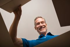 Man opening box. Happy mature man looking into parcel cardboard box and smiling. Cheerful senior man happy on seeing package. Smiling man feeling overjoyed on Stock Image