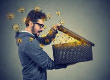 Man opening a box with many bright light bulbs Royalty Free Stock Photo