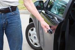 Man opening car door. Caucasian man opening car door of black land vehicle Stock Photography