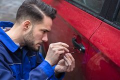 Man Opening Car Door With Lockpicker. Young Man Opening Red Car Door With Lockpicker Royalty Free Stock Photo