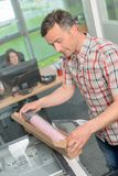 Man opening cardboard box on photocopier stock image