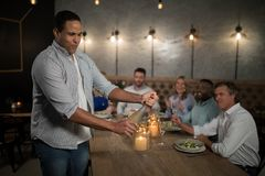 Man opening champagne bottle Stock Images