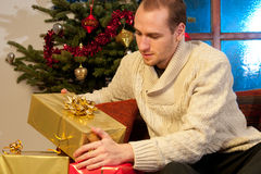 Man opening christmas gifts. White young man enjoying christmas presents Stock Image