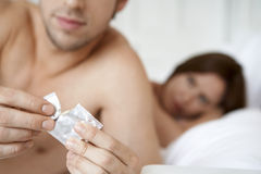Man Opening Condom With Woman In Bed. Young men opening condom with women in bed Stock Image
