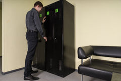 Man opening the door of a filing cabinet Stock Image