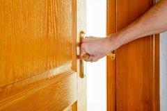 Man opening a door to get out. A man is opening a wooden door with a metallic handle to get out of a room and enter in an illuminated one royalty free stock images