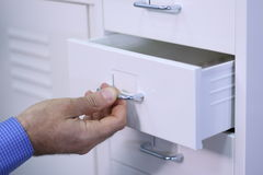 Man opening a drawer in a cabinet. Cropped view image of a male hand opening a small drawer in a white cabinet Royalty Free Stock Photo