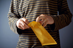 Man opening envelope. Casual man is opening yellow document postal envelope Royalty Free Stock Images