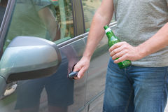 Man opening his car while holding a bottle of beer Stock Photography
