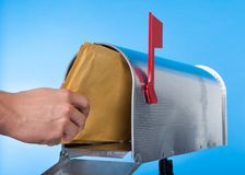 Man opening his mailbox to remove mail. Inside  close up of his hand on the open door against a blue sky Royalty Free Stock Photo