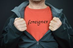 Man opening jacket showing word FOREIGNER. A man opening his jacket and showing the word FOREIGNER on his red t-shirt under it royalty free stock photo