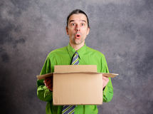 Man opening a package and looking surprised Stock Image