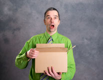 Man opening a package and looking surprised Stock Photo