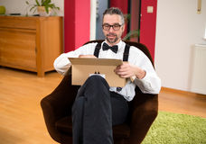 Man opening a package. Young bearded man in white shirt with bow-tie  opening a package Royalty Free Stock Photo